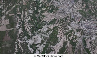 Aerial view of rocky mountains with roads and city view