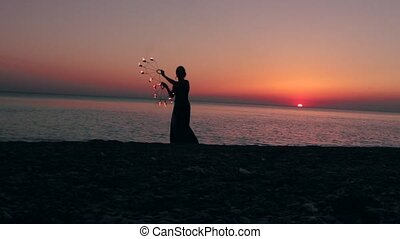 girl manages fire near the sea at sunset - silhouette of a...