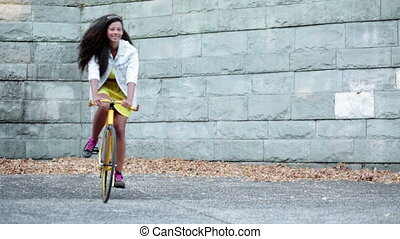 Girl riding on yellow bike - Happy ethnic girl riding on...