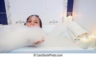 Young beautiful woman playing with foam in bathtub...