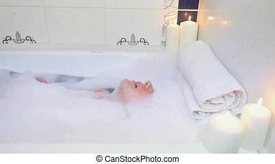 Beautiful young woman washing her hair in bathtub with foam