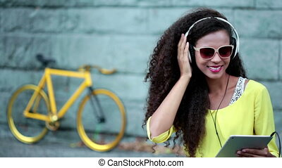 Woman listening music - Woman with headphones and tablet...