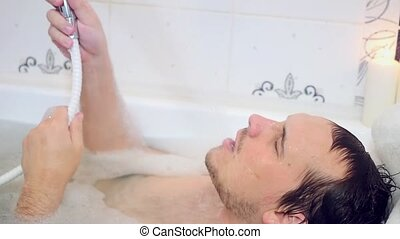 Sexy man lies in bathtub pouring water over his head taking...