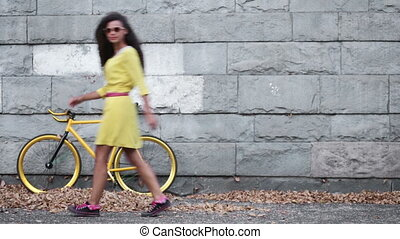 Girl in yellow dress walking backwards and forwards