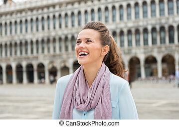 Laughing woman tourist on St. Mark's Square looking up -...