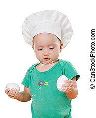 adorable little baby in a chef's hat, preparing meal of eggs. Isolated on white