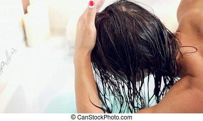 Young beautiful woman relaxing in a bath, washing herself hair