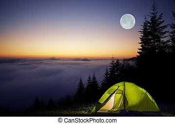 Tent Camping in a Forest During Full Moon Night. Foggy...