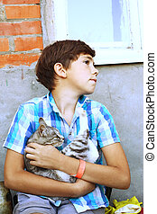 preteen handsome country boy with kitten close up portrait -...