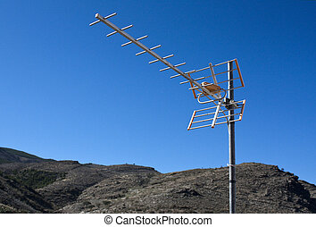 TV Aerial - TV aerial with mountains and blue sky as...