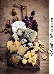Cheese plate served with grapes, jam, crackers and nuts on a...