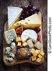 Cheese plate served with grapes, jam and figs on a wooden...