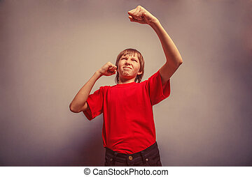 Boy, teenager, twelve years red in shirt, showing fists his...