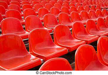 Grandstand stadium - Empty plastic chairs of red color are...