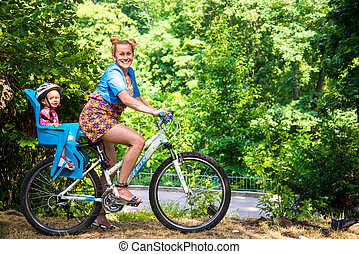 Mom on a bike with a small child, who wore a bicycle helmet...