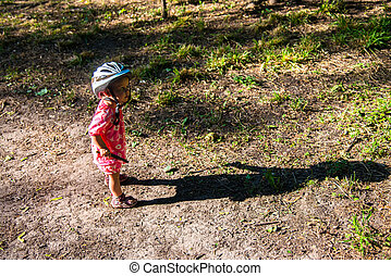 Little girl in a sundress and bicycle helmets