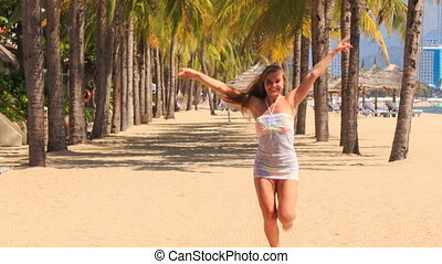 blonde girl in lace runs between palms row approaches camera...