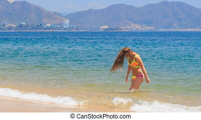 blonde girl in bikini runs out of water shakes wet long hair