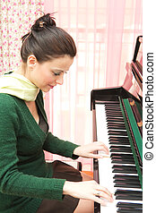 Beautiful pianist - Beautiful young woman playing the piano...