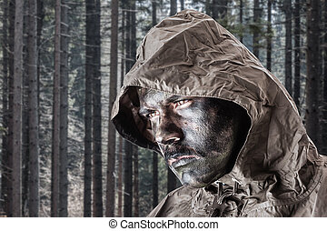 Soldier in the woods - a soldier wearing a poncho o raincoat...