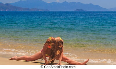 blonde girl in bikini makes split on wet sea sand wave hands...