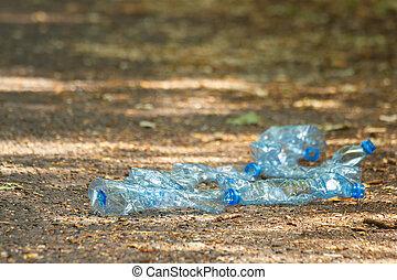 Plastic bottles of mineral water on path in park, littering...