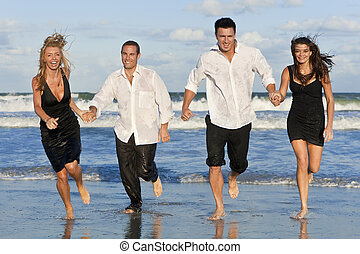 Four Young People, Two Couples, Having Fun Running On Beach