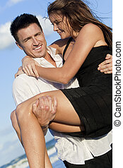 Romantic Couple On Beach With The Man Carrying his Woman - A...