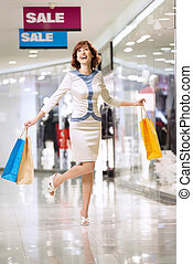 Shopaholic - Beautiful happy woman laughs in shop on sale