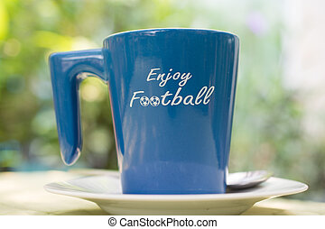 Coffee cup with the word enjoy football on its side.