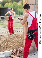 Builders at house construction site - Two builders working...