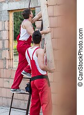Building workers during work - Building worker is giving...