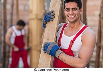 Smiling building worker holding timber at building site