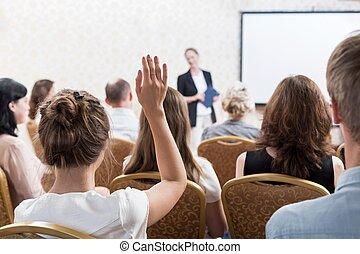 Listener raising hand to ask - Photo of listener raising...