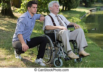 Retired person and male carer - Photo of disabled retired...