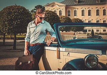 Confident wealthy young man with briefcase near classic...