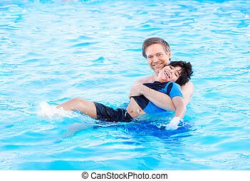 Father swimming in pool with disabled child