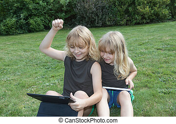 Boy won the game on a tablet - Two blond brothers are...