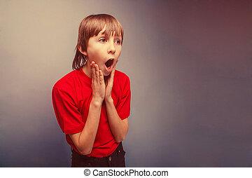 Boy, teenager, twelve years in the red shirt surprised open...