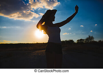 woman in a cowboy hat photographing themselves self blue sky...