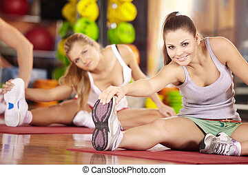 Stretching - Two smiling girls do exercise in sports club