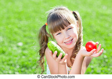 Happy little girl sitting on the grass with vegetables at day time. Concept of healthy food.