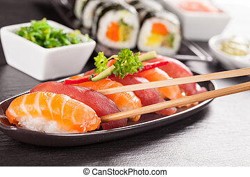 sushi pieces with chopsticks - sushi pieces served on black...