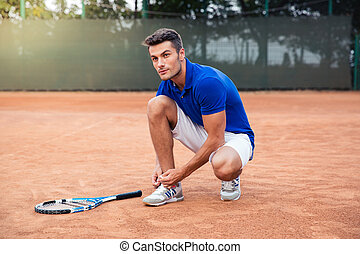 Male tennis player tying shoelaces - Handsome male tennis...