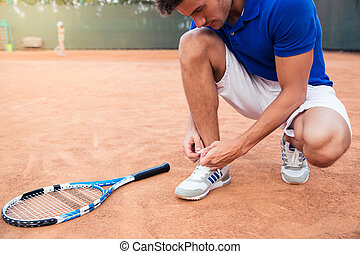 Male tennis player tying shoelaces outdoors