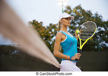 Portrait of a pretty female tennis player standing outdoors