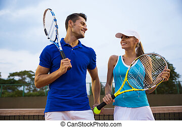 Tennis players talking at the court - Couple of tennis...