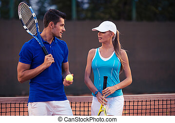 Couple talking at tennis court - Portrait of a young couple...