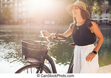 Happy woman at the park with a bicycle