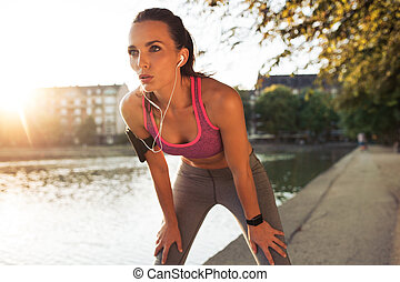 Young sportswoman resting after run - Female runner standing...